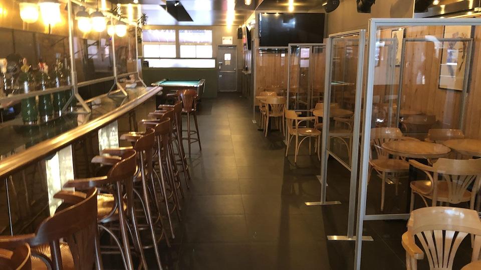 Un bar vide avec des tables séparées par des panneaux de plexiglas.
