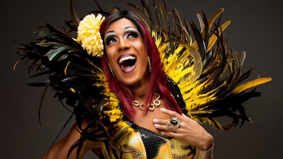 Barbada pose dans un costume de plumes noires et jaunes avec une fleur sur la tête.