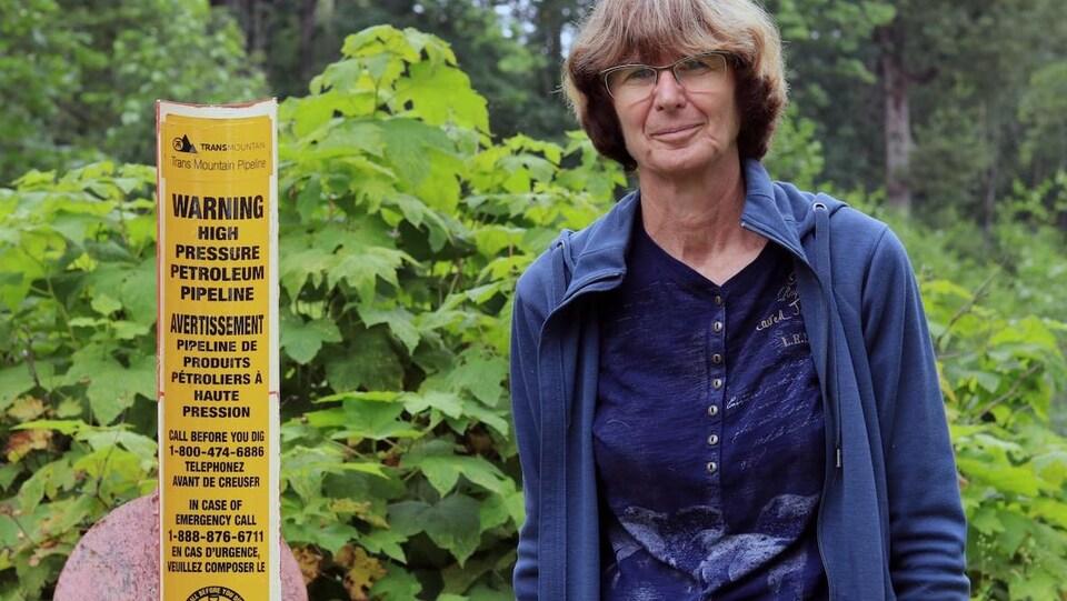 Une femme pose en forêt devant une affiche de Trans Moutain sur sa propriété.