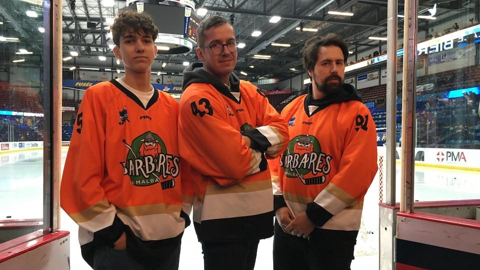 Trois hommes en maillot de sport dans un aréna.
