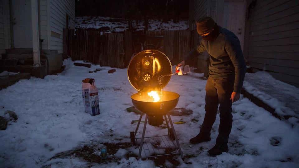Un résident du Texas, dans sa cour, se prépare à manger sur son barbecue.