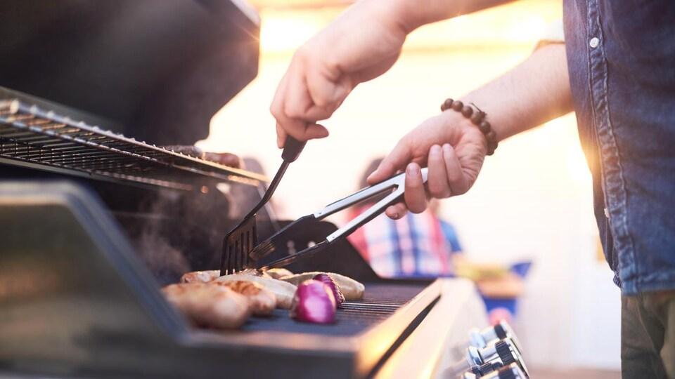 Un homme cuisine des saucisses et des oignons sur un barbecue.