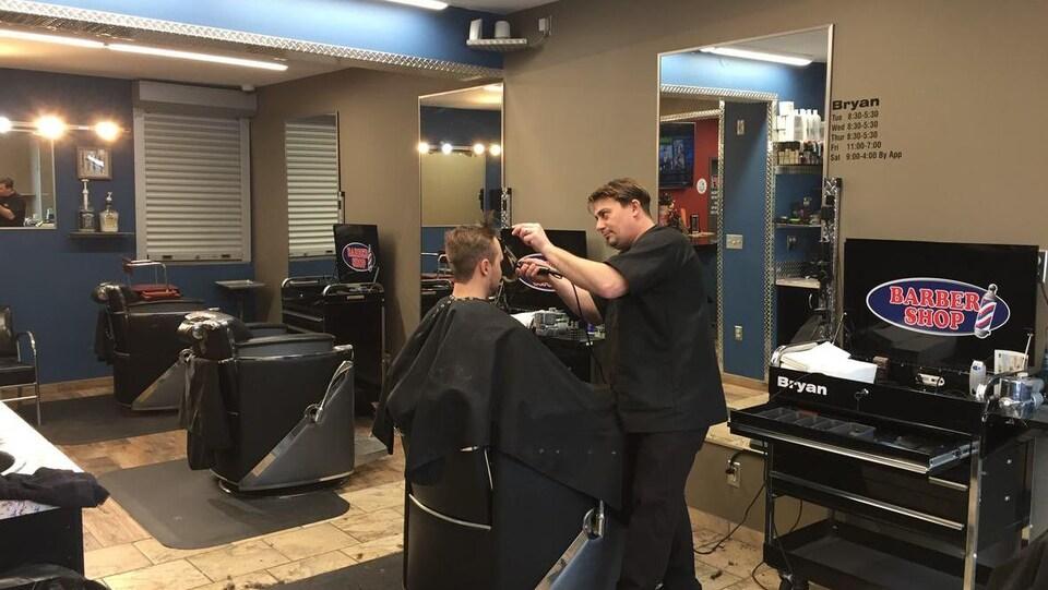 Un barbier en train de couper les cheveux d'un homme.