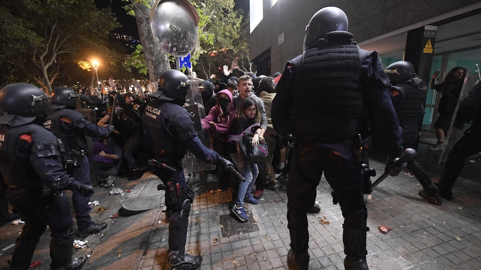 Des manifestants reculent devant les policiers antiémeutes.