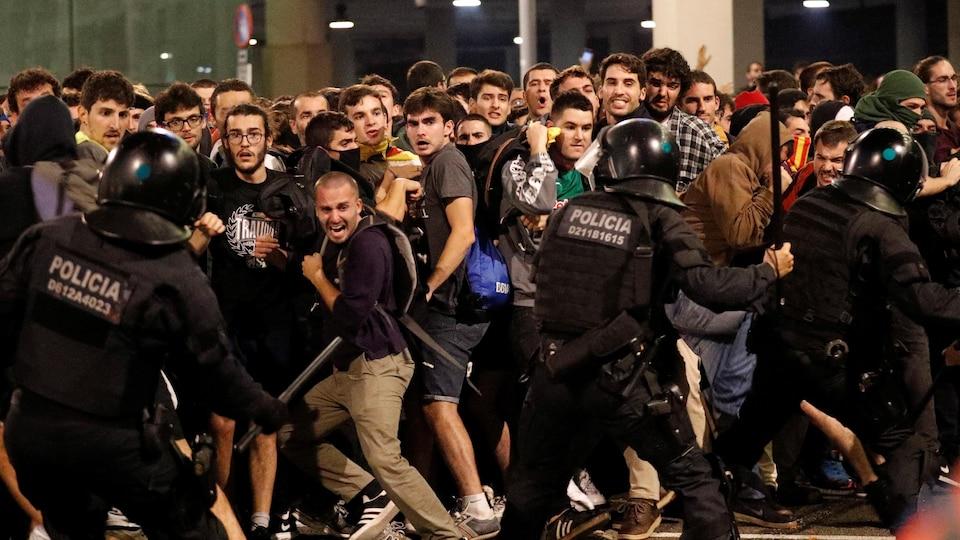 Des manifestants affrontent des policiers qui brandissent des matraques.