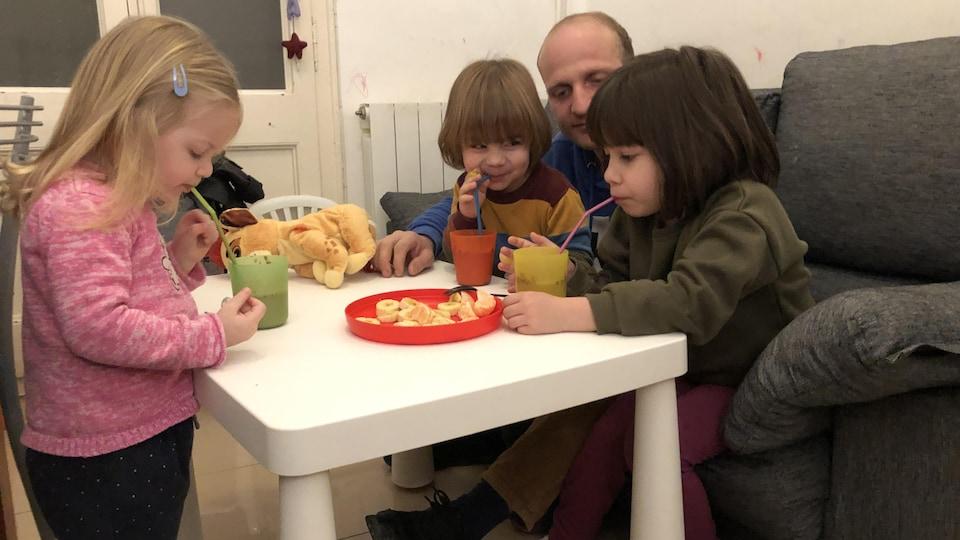 La petite famille autour de la table du salon.