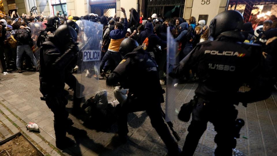 Un homme à terre frappé par des policiers, en arrière-plan des manifestants massés devant un immeuble.