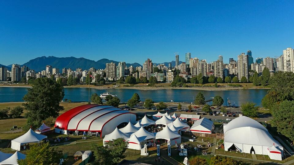 Plusieurs tentes de différents formats au bord de l'eau avec une ville et des montagnes en arrière-plan