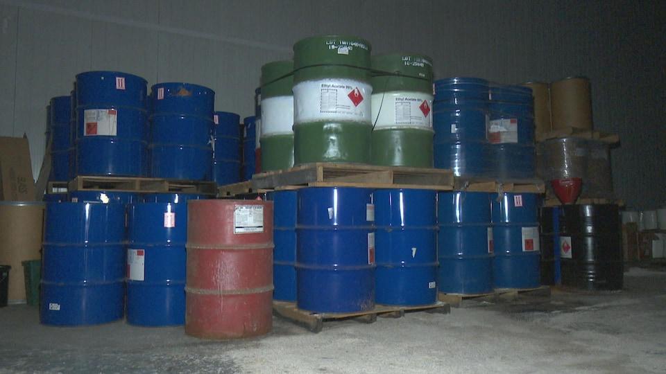Une vingtaine de barils contenant des produits chimiques entreposés dans une salle sombre.