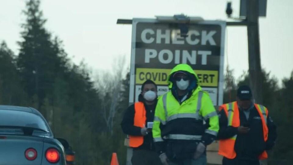 Trois personnes munies de masques sont debout près d'une voiture à un barrage routier.