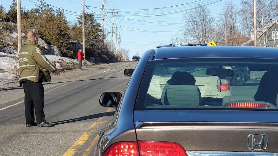 Des voitures arrêtées et un policier sur la route 132.
