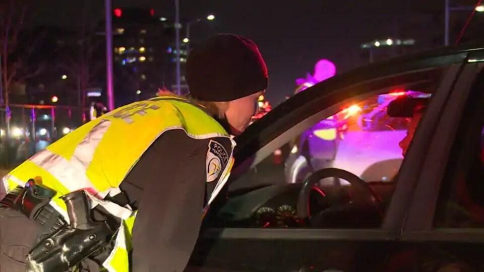 Une policière parle avec un automobiliste.