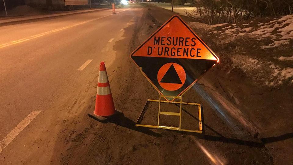 Un barrage routier de la Sûreté du Québec, qui vise à  restreindre les visites non essentielles dans certaines régions du Québec, afin de limiter la propagation de la COVID-19 au sein de la population. On aperçoit une plaque de signalisation.