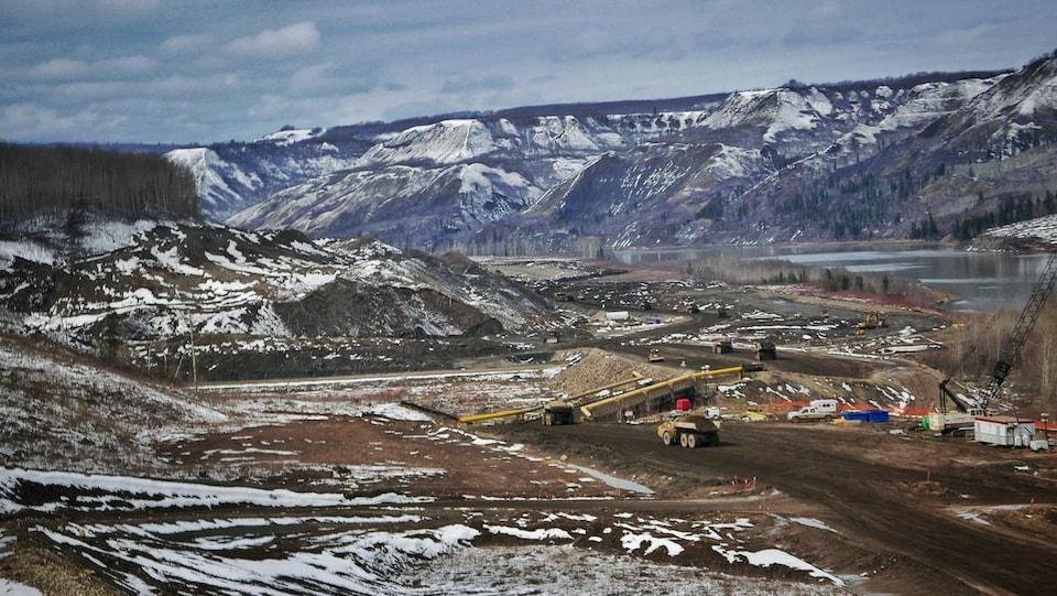 Plan panoramique d'un chantier de construction dans une vallée traversée par une rivière, le tout partiellement recouvert de neige.