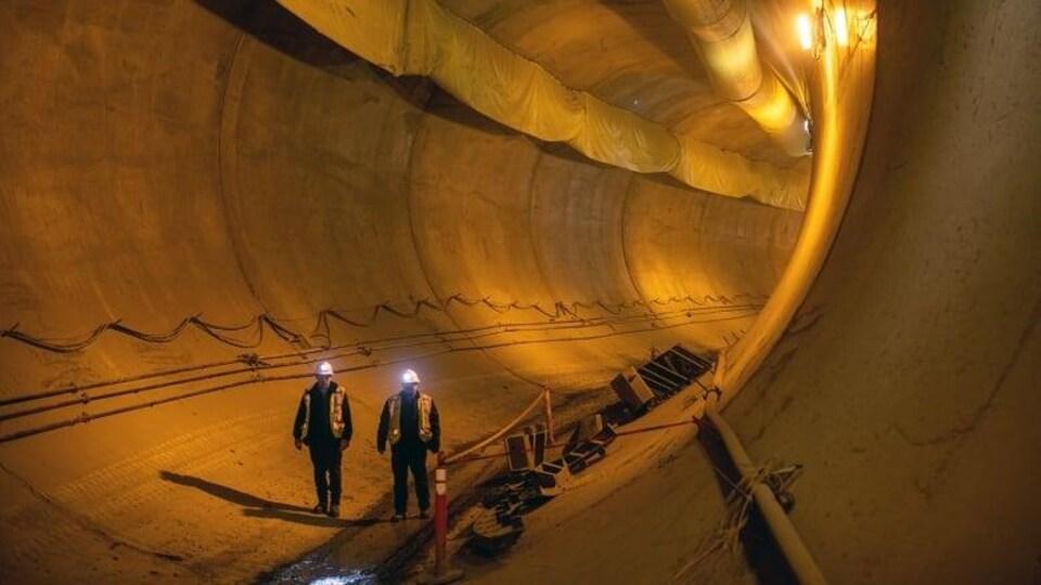 Deux ouvriers marchent dans un énorme tunnel.