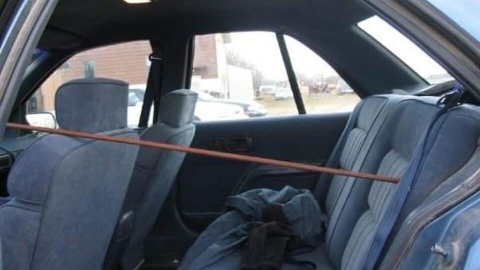 Photo prise de la portière passager gauche. Une barre de fer traverse horizontalement la voiture et est plantée dans le coffre.