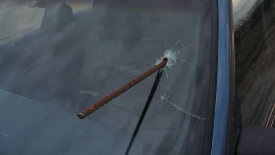 Le pare-brise d'une voiture transpercé par une barre de fer au niveau de la tête du conducteur