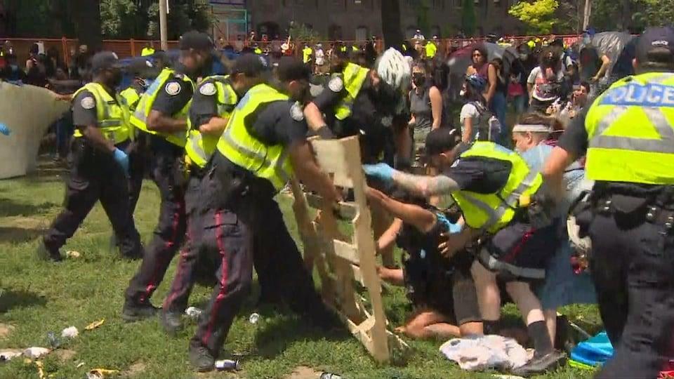 Plusieurs policiers saisissent une palette de bois