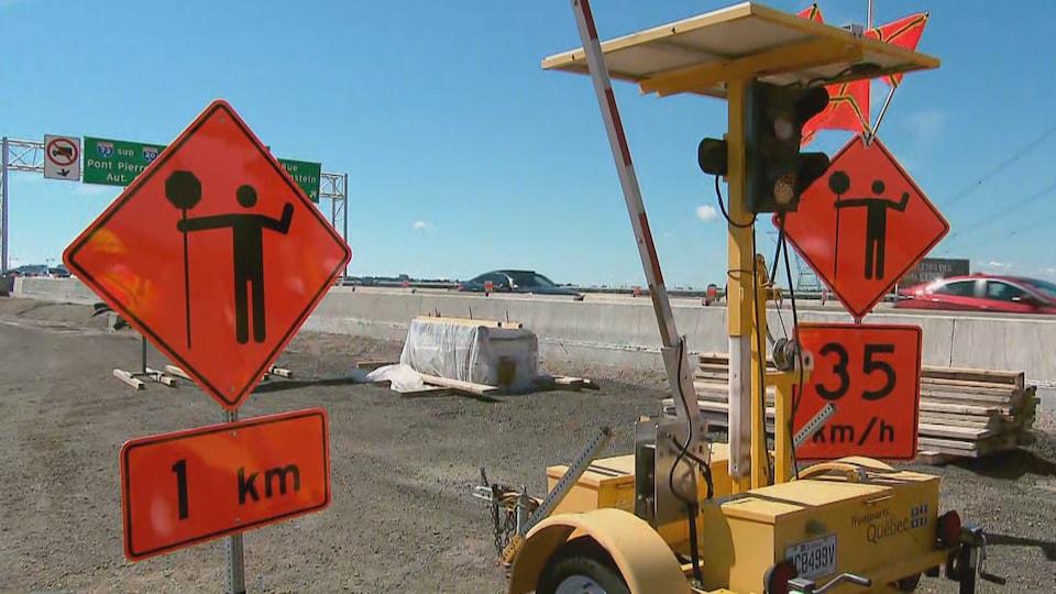 Une barrière mobile pour chantier de construction accompagnée de panneaux de signalisation orange.