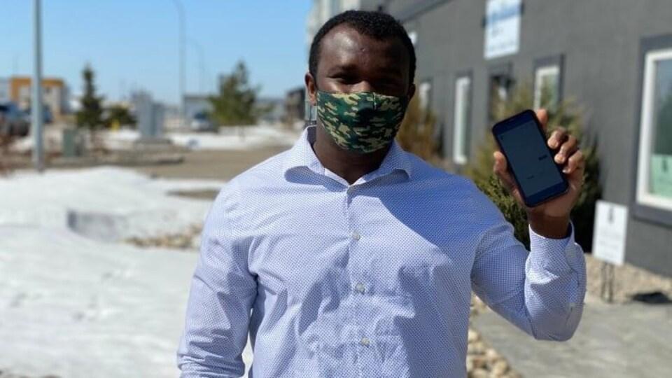 Barry Vopnu à l'extérieur, portant un masque et tenant son téléphone dans la main gauche.