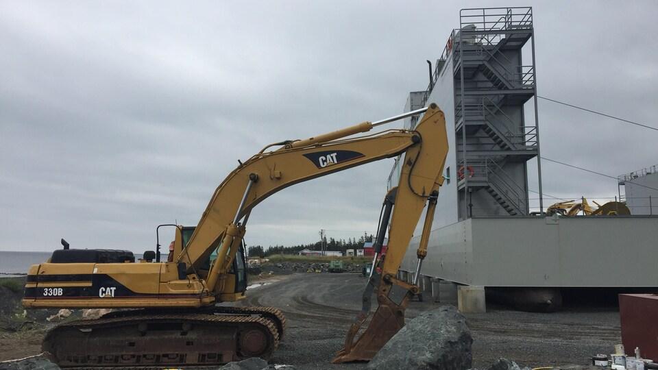 Une excavatrice garée à côté de la cale sèche à deux pas de la mer