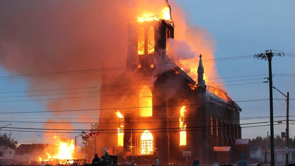 Des flammes sortent de l'église embrasée.
