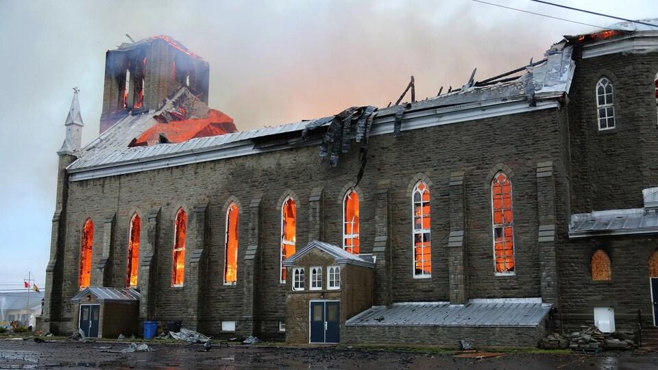 La lueur des flammes éclaire l'intérieur de l'église en ruine.