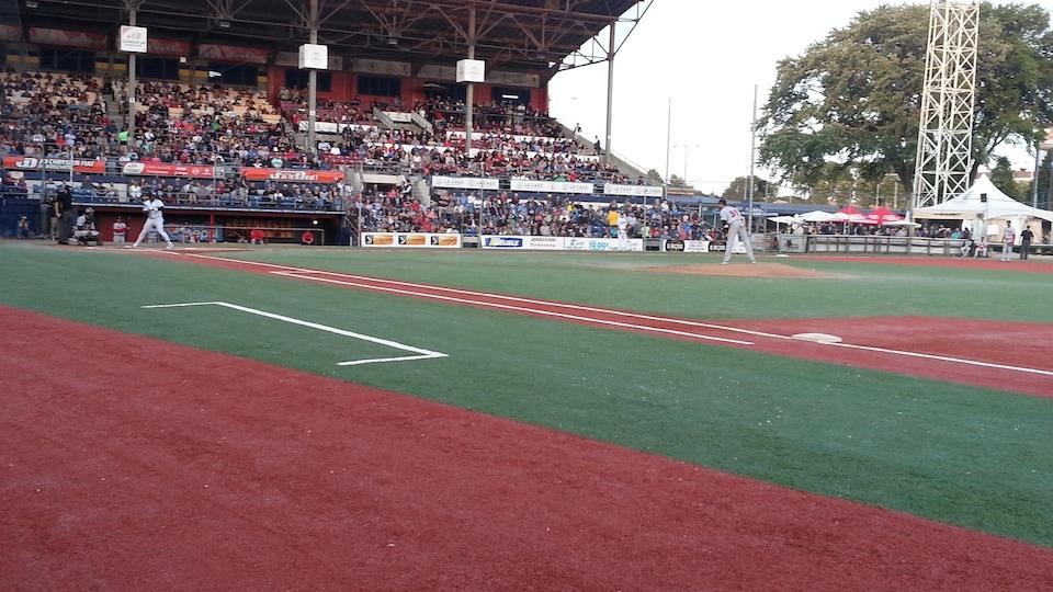Terrain de baseball avec gradins à l'arrière.