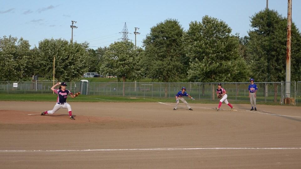 Le 16 août 2017, au parc Martin-Bergeron lors de la finale, une joueuse qui lance la balle, pendant que l'autre guette le joueur sur le but.