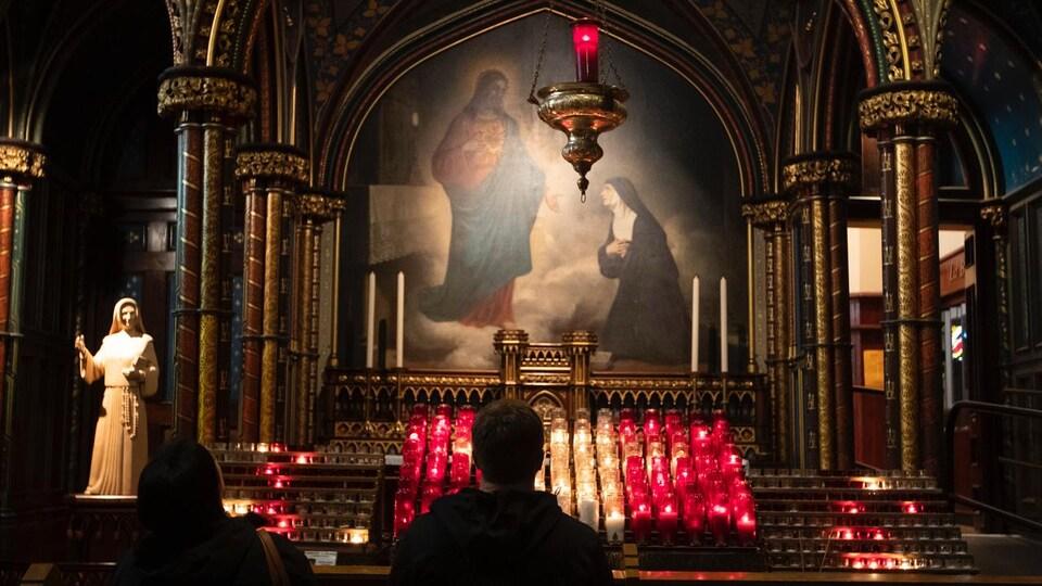 Deux fidèles, de dos, se recueillent devant des lampions et une photo religieuse.