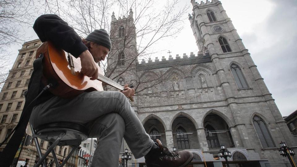 Un musicien joue de la guitare dans le parc situé devant la basilique Notre-Dame.