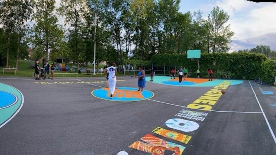 Une dizaine de personnes se promènent sur un terrain de basketnball.