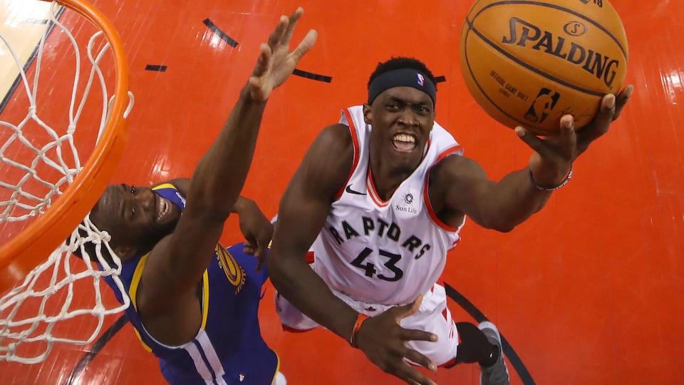 Un joueur saute près du panier avec le ballon dans la main gauche; un défenseur tend le bras pour le bloquer.