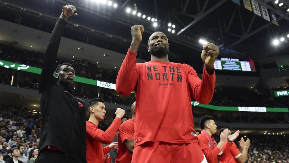 Un joueur des Raptors Serge Ibaka, porte un haut rouge avec le slogan We the North sur le bord du terrain de Basketball.