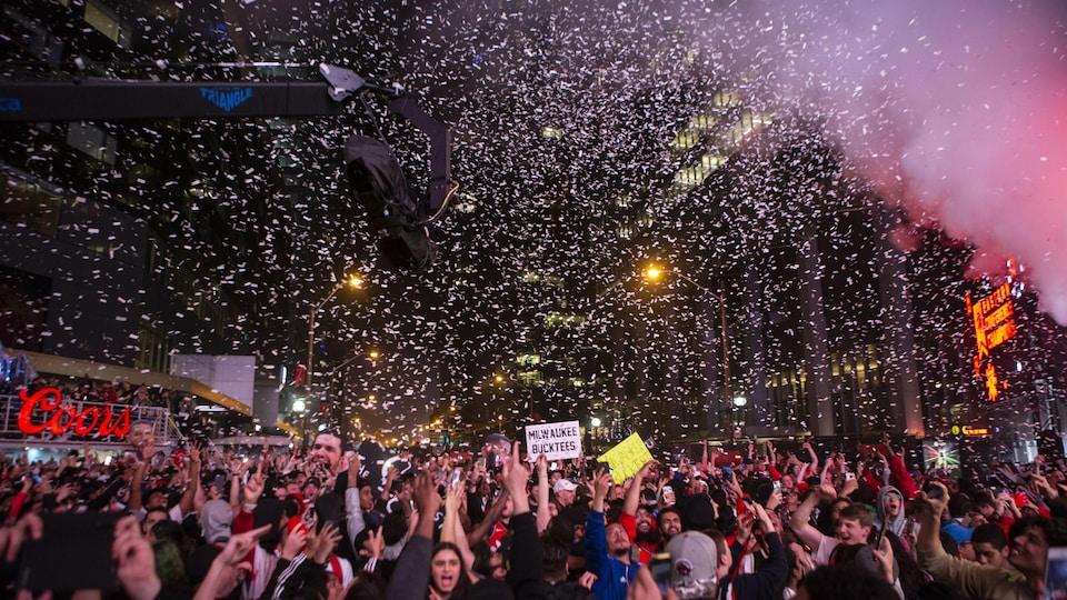 Des confettis pleuvent sur une foule rassemblée pour célébrer la victoire des Raptors de Toronto.