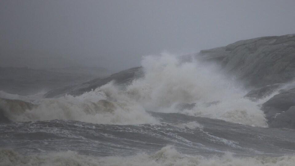Des vagues viennent se briser sur les rochers.