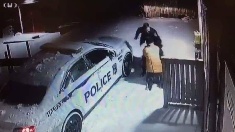 Les deux hommes sont entre la voiture du policier et l'édifice du refuge durant la nuit.