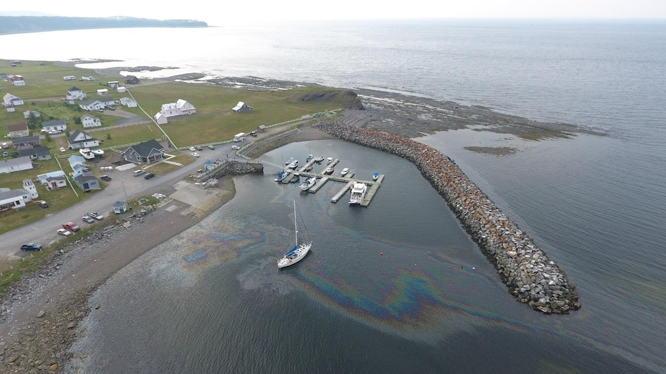 Du carburant fait une trace arc-en-ciel dans l'eau de la marina de Rivière-la-Madeleine.
