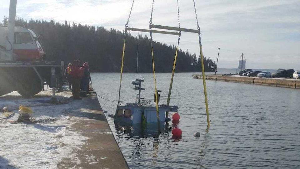 Le dessus d'un bateau coulé émerge de l'eau et est attaché à une grue qui va le repêcher.
