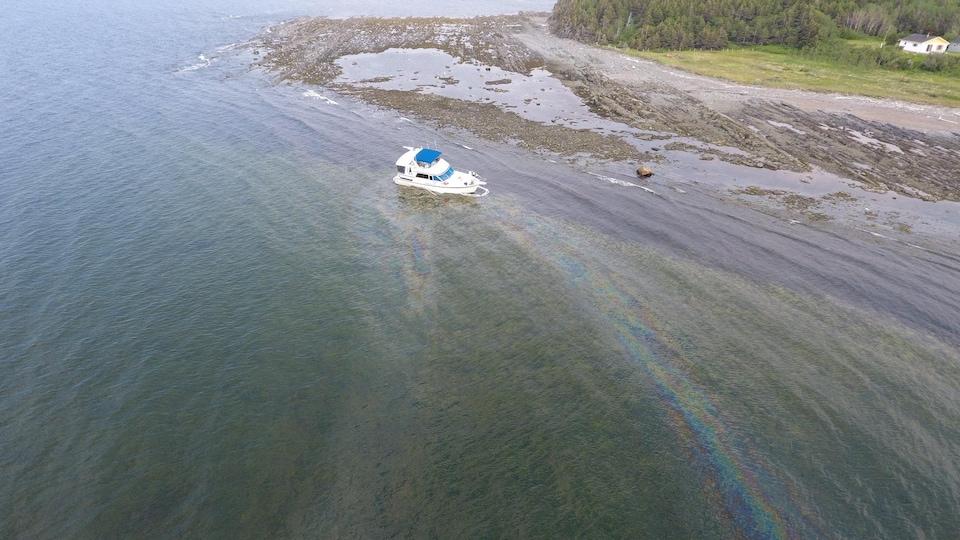 Une trace d'huile s'échappe du bateau échoué.