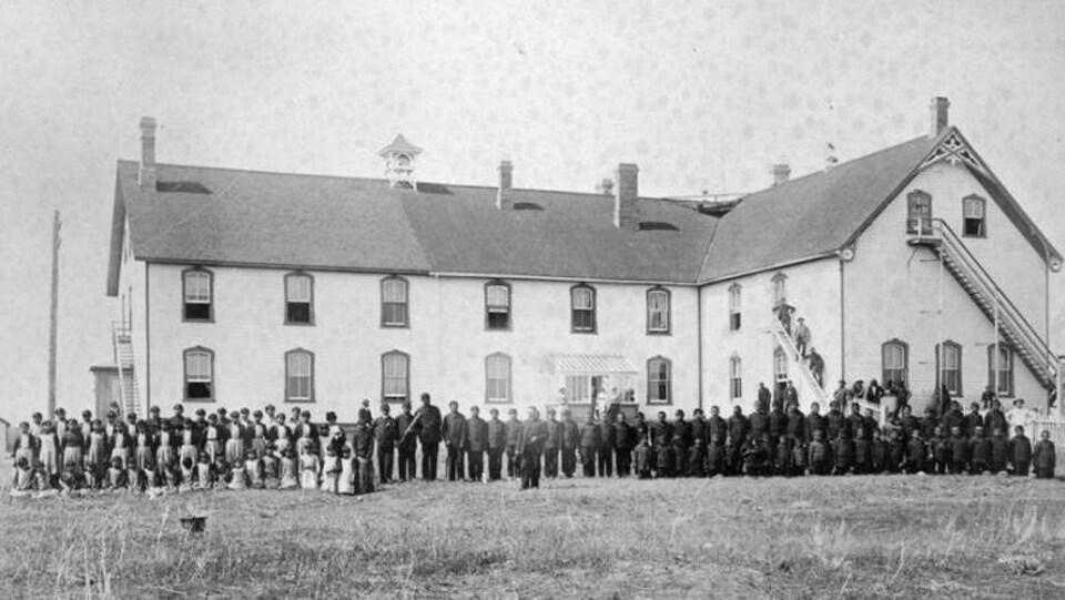 Des élèves debout devant le pensionnat autochtone Battleford Industrial School en 1895 qui comprend deux étages.