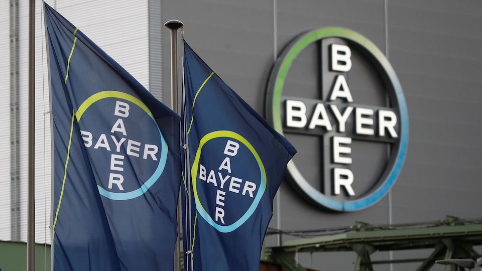 Des drapeaux et un logo géant de l'entreprise devant une de ses usines.