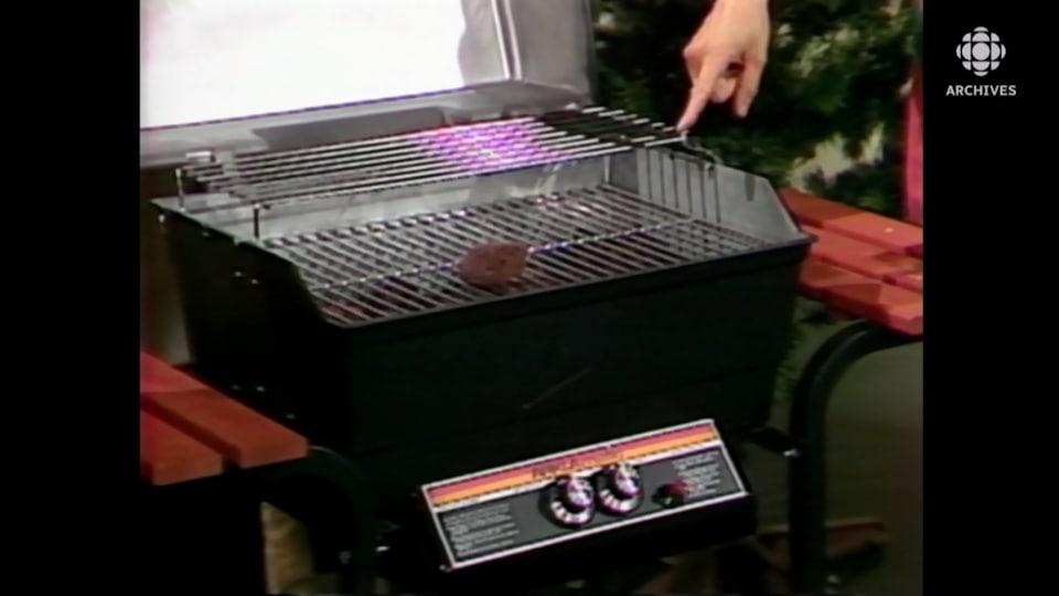 Un doigt pointe un modèle de barbecue avec deux brûleurs et deux tablettes sur le côté.