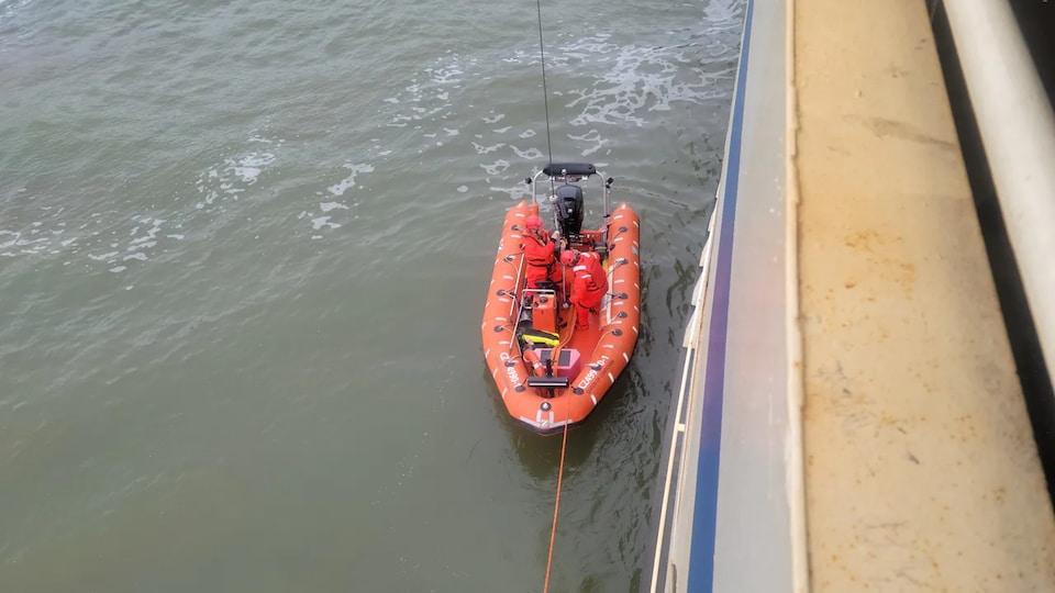 Un bateau de sauvetage de BC Ferries est sur l'eau à côté de la coque du traversier Queen of Cowichan.