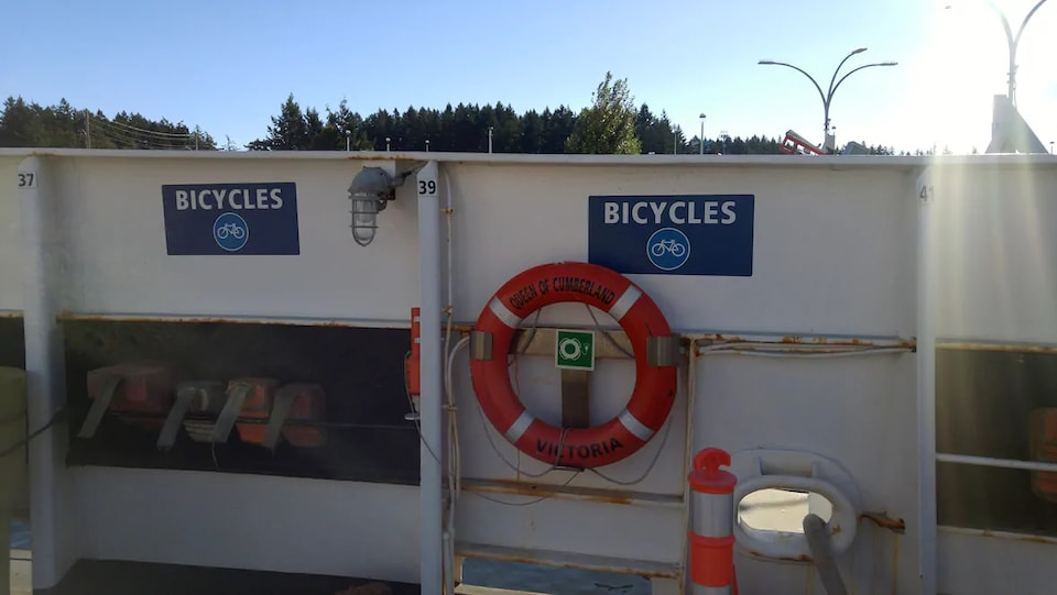Une affiche où est écrit bicycles est posée près d'une bouée de sauvetage.