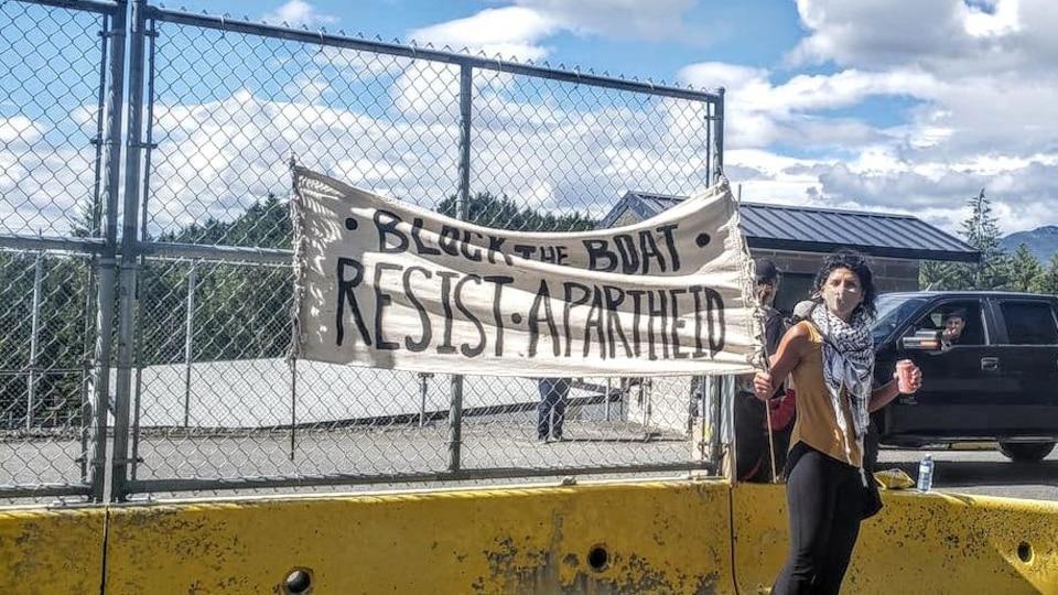 Une manifestante brandit une affiche qui indique Block the Boat : Resist Apartheid (Bloquez le navire, résistons à l'apartheid).