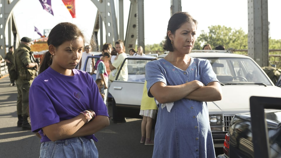 Une mère et sa fille, les bras croisés, sur un pont. On aperçoit plusieurs véhicules et personnes derrière elles, ainsi que des militaires.