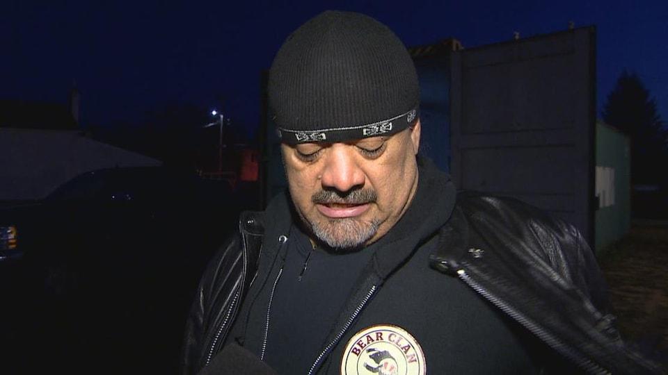 Un homme avec une barbe et un bonnet noir regarde le logo sur son pull noir. C'est un rond blanc cassé sur lequel est inscrit Bear Clan.