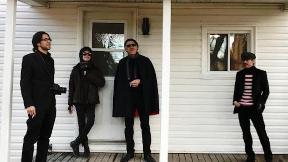 Quatre personnes habillées uniformément en noir ont des airs détendus sur le perron avant d'une maison. Ils fument la cigarette.