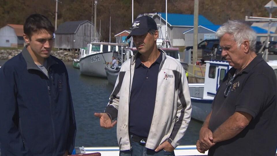 Les trois hommes debout sur un quai devant des bateaux de pêche au homard.